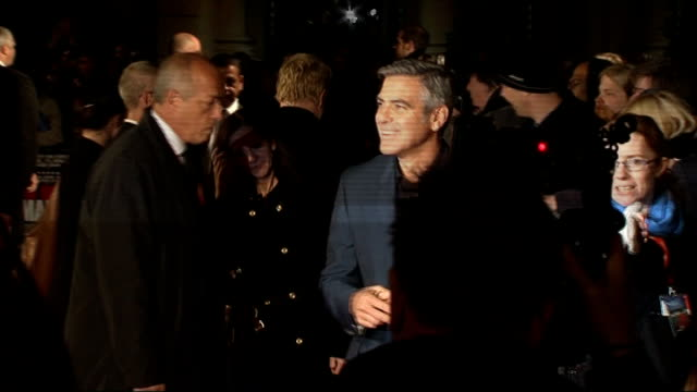 George Clooney attends premiere of 'The Ides of March' Long shot of Clooney signing autographs for fans / Clooney posing next Philip Seymour Hoffman...