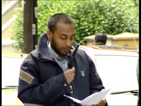 London Finsbury Park Prayer meeting outside home of arrested Muslim cleric Abu Hamza as police officer looks on in f/g MS Man preaching MS SIDE Men...
