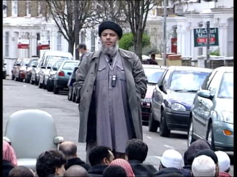 vídeos y material grabado en eventos de stock de finsbury park radical muslim cleric sheikh abu hamza preaching to his followers in the street zoom in cbv follower of abu hamza laying down prayer... - alfombra de oración