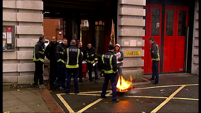 london firefighters strike; england: london: ext wide shot firefighters on strike in front of fire station burning small fire / gv striking... - newspaper strike stock videos & royalty-free footage