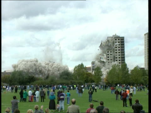 flats demolished; 18.20 england: london: hackney tgbv people standing on grass facing tower blocks zoom in two tower blocks as one collapses as... - hackney stock videos & royalty-free footage