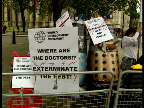 london g8 meeting / debt relief deal agreed; ext gv daleks protesting to exterminate third world debt daleks holding placards... - debt stock videos & royalty-free footage