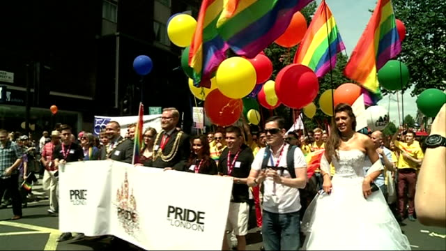 london gay pride parade 2013 vox pops people marching with 'pride london' banner and balloons barechested men holding placards marchers wearing... - 胴体点の映像素材/bロール