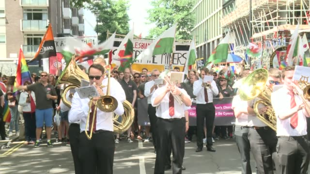 london ext brass band leading 'support the miners' group in the gay pride march people watching parade and waving flags police officers along in... - brass band stock videos & royalty-free footage