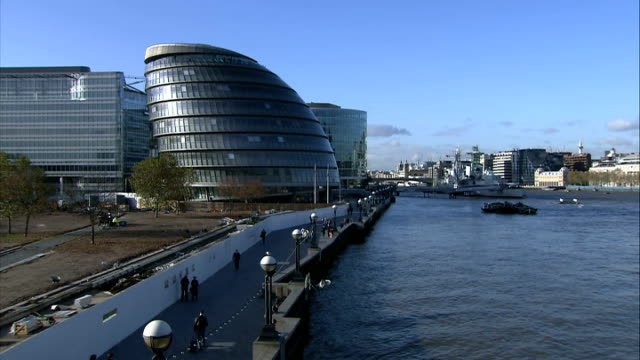 General views of landmark sites City Hall General view of GLA building from Tower Bridge with Pool of London and people walking along embankment