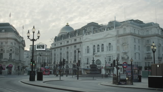 london going back to work, piccadilly circus, eros statue and underground station during coronavirus pandemic with cyclist and red bus - no people stock videos & royalty-free footage