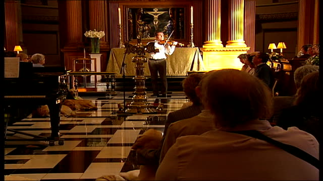 London Guide Dogs 75th year celebrations / general views of people and guide dogs at special church service Man playing a violin as part of church...