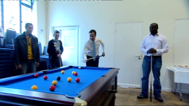 hammersmith: int conservative party leader david cameron mp potting red ball in game of pool during visit to the spear project and then missing... - vacancyサイン点の映像素材/bロール