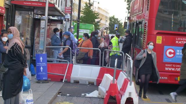 london - harlesden  - high street in poorer neighbourhood people boarding bus sunny day - image stock videos & royalty-free footage