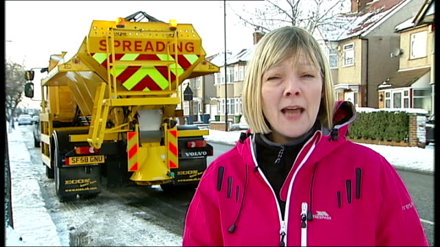 reporter to camera with handful of salt grit spreader along and past up road cllr susan hall interview sot int car shot showing grit spreading lorry... - harrow stock videos & royalty-free footage