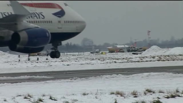 london heathrow airport side shot of british airways plane taxiing side shot of ba plane taxiing slowly with snow ploughs at work behind gvs snow... - hands behind head stock videos and b-roll footage