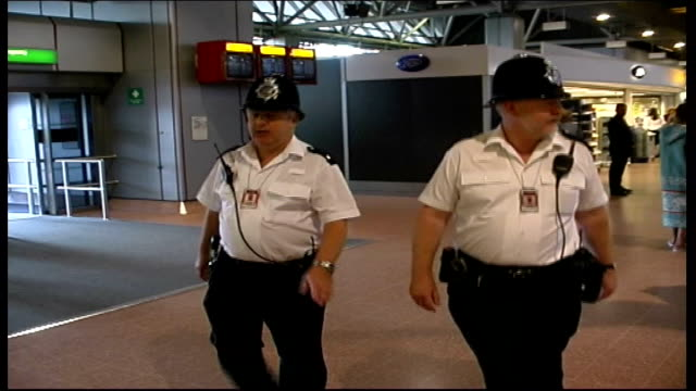 London Heathrow Airport INT 4757 Two police officers walking along past passengers in terminal building more ditto BV police officers along police...
