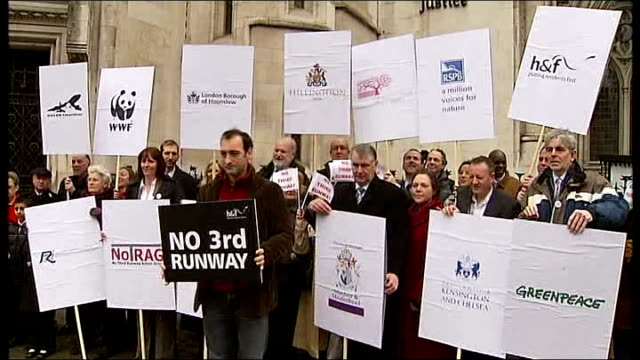 high court: ext alistair mcgowan and other protestors holding up 'no third runway' signs outside high court, sign outside court and group of... - アリステア マクゴワン点の映像素材/bロール