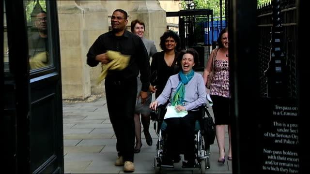 london: house of lords: ext debbie purdy along in wheelchair with omar puente - puente stock videos & royalty-free footage