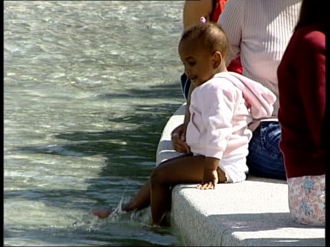 london hyde park princess diana memorial fountain with no water in it as water appears ms side children sitting on side of fountain with feet in... - swimming costume stock videos & royalty-free footage
