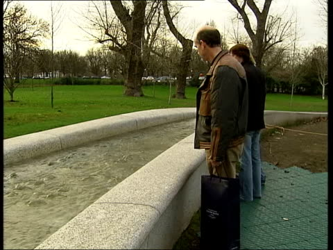 hyde park: ext people walking round the princess diana memorial fountain man taking photograph of fountain as woman and boy look on lms side man... - turf stock videos & royalty-free footage