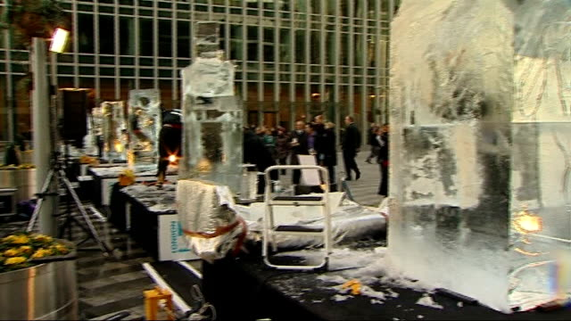 london canary wharf ext ice sculptor using chainsaw to cut through block of ice at the london ice sculpting festival teams working on ice blocks as... - sculptor stock videos & royalty-free footage