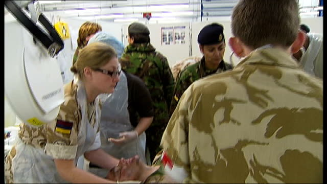**all 'injured' soldiers int army medical staff treat wounded british soldier in mock up of camp bastion field hospital during training exercise... - fake hospital stock videos & royalty-free footage