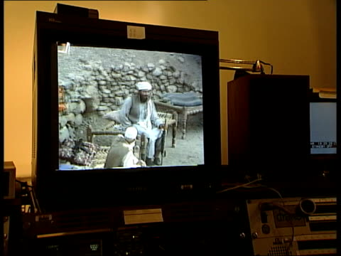 London BV Brigadier John Almonds watching secretly filmed video of Taliban MS Television screen showing pictures of Taliban unit outside cave...