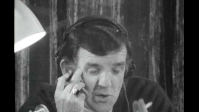 london int b/w footage **music heard sot** alan freeman broadcasting radio show while smoking cigarette sot pull back studio engineer producer... - radio jockey stock videos & royalty-free footage