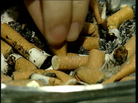 london int css hands stubbing out cigarettes cs hand holding lit cigarette - zigarettenstummel stock-videos und b-roll-filmmaterial