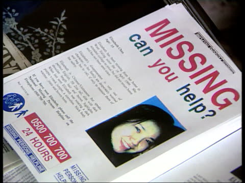 london int ms family of missing nineteen year old girl elizabeth chau sitting in living room round table covered with missing posters cms missing... - poster stock-videos und b-roll-filmmaterial