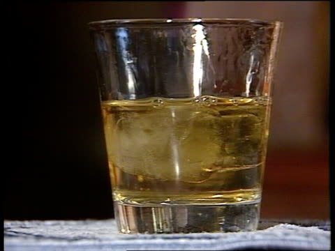 London INT CU Glass of whisky ice dropped into it in Green Man pub EXT MS Downandouts ZOOM TS One asleep on pavement INT CMS Two drink in pub CMS...