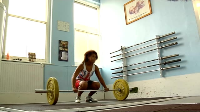 vídeos de stock e filmes b-roll de zoe smith stood in front of camera in gym wearing tracksuit / smith stood wearing weightlifting gear various shots of smith dropping weights onto... - fato de treino