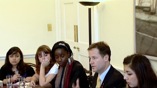 london int nick clegg mp sitting for breakfast meeting with students clare solomon standing wearing white tshirt with message 'coalition plot blows... - ニック クレッグ点の映像素材/bロール