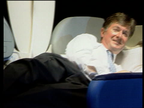 london outgoing british airways chief executive bob ayling reclining in new business class seats stewardess pull out ayling - zurücklehnen stock-videos und b-roll-filmmaterial