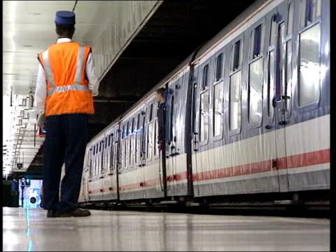 London Passengers onto train Guard blowing whistle
