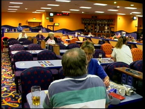 stockvideo's en b-roll-footage met london side bingo caller speaking into microphone la gv digital bingo number screen numbers being ticked off on bingo card rob hayward interview sot... - bingo