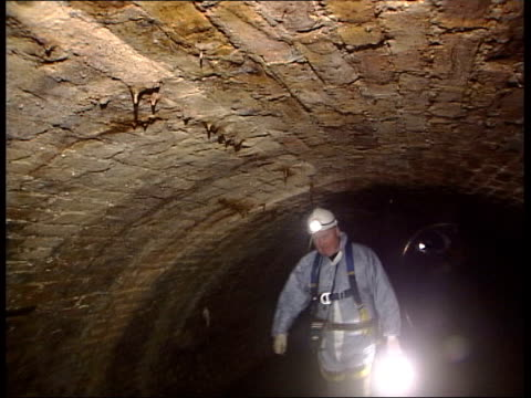 vídeos de stock, filmes e b-roll de london various engineers clarke along thru sewage tunnels in hard hats and protective clothing i/c wearing hard hat in tunnel - esgoto