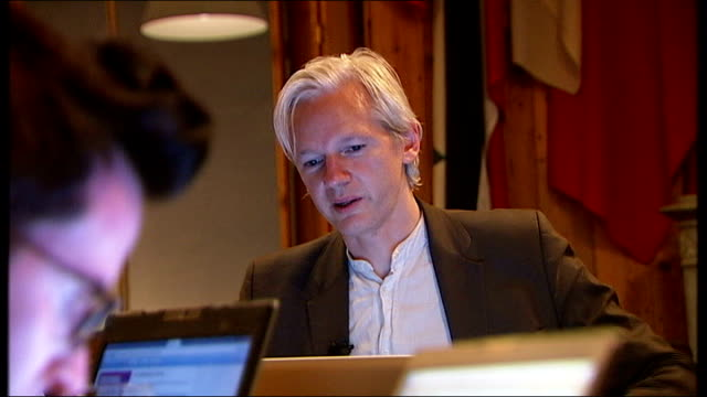 london int various views of julian assange seated with two journalists looking at laptop screens including close ups of assange - 2010 video stock e b–roll