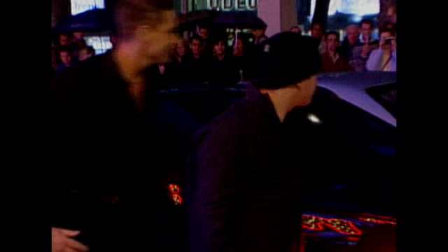 stockvideo's en b-roll-footage met london leicester square ext / night **beware exterior of empire cinema stephen gately and boyfriend arriving at 'billy elliot' film premiere and... - boyzone
