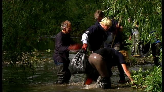 vidéos et rushes de lewisham: river pool: ext london mayor boris johnson helping volunteers clear debris from river boris johnson falls over in river as picking up... - boris johnson