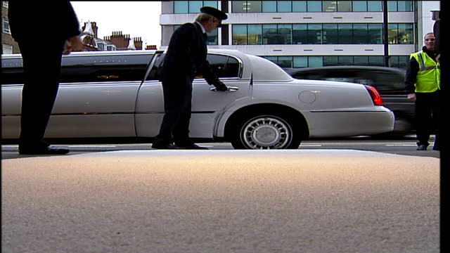 london madame tussauds ext / dusk * * intermittent flash photography * * stretched limousine arriving low angle shot of chauffeur opening limo door... - limousine luxuswagen stock-videos und b-roll-filmmaterial