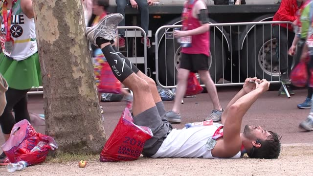 sir mo farah sets new british record in hottest london marathon on record the mall runner posing with medal man lying down by tree runner along in... - environmental media awards stock videos & royalty-free footage