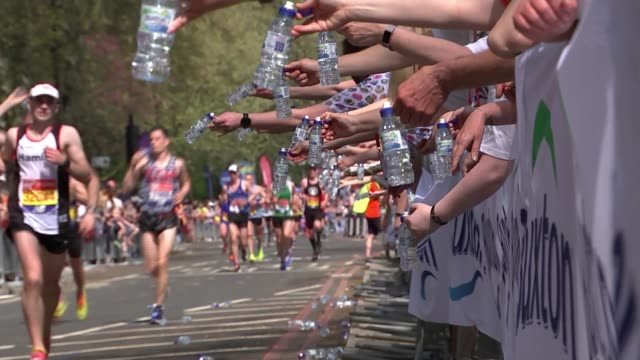 vídeos y material grabado en eventos de stock de sir mo farah sets new british record in hottest london marathon on record; england: london: the mall: ext london marathon runner jumping in air as... - línea de meta