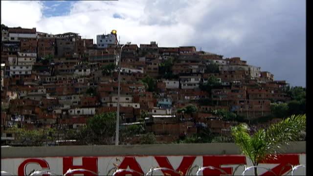 london mayor ken livingstone flies home after aborted venezuela trip tx caracas ext slum dwellings on hillside including graffitti promoting hugo... - ウゴ・チャベス点の映像素材/bロール