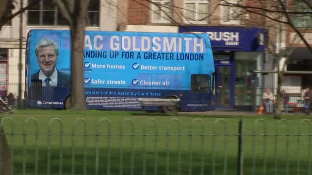 stockvideo's en b-roll-footage met campaign descends into namecalling ext double decker bus along street with 'zac goldsmith standing up for greater london' sign on side goldsmith bus... - street name sign