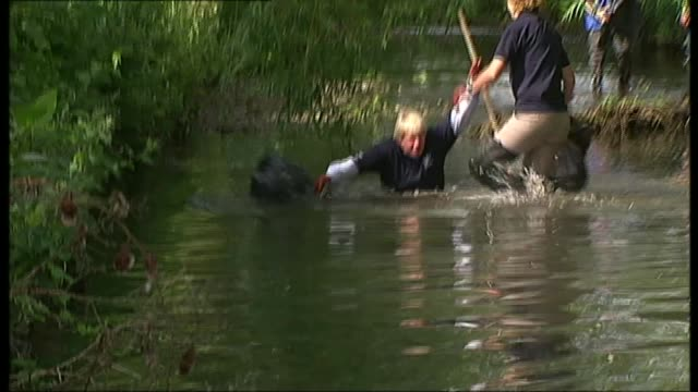 london mayoral election: a look back at boris johnson's 8 years in office; t04060910 johnson wading along stream with volunteers who are clearing up... - falling stock videos & royalty-free footage