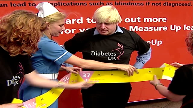 london mayoral elections: boris johnson at diabetes uk roadshow; large tape measure being wrapped around johnson's waist - tape measure点の映像素材/bロール
