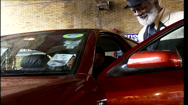 London mini cab driver campaigns against restrictions against private hire vehicles Side view of Humes assisting a disabled customer into his minicab...