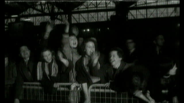 london: **music overlay: bill haley and the comets - 'rock around the clock'** b/w american rock and roll star bill haley standing at door of train... - b roll stock-videos und b-roll-filmmaterial
