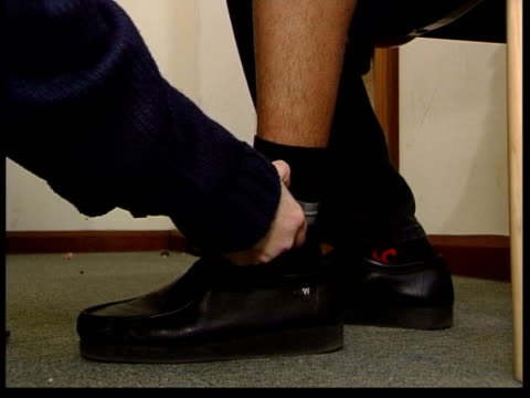 lib london newham seq woman fitting electronic tag to ankle of offender man testing tag of offender in his home - tag 2 stock-videos und b-roll-filmmaterial