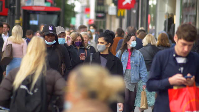 london oxford street west end shoppers crowd slomo 50% masked 2021 sunny day medium close up - pedestrian stock videos & royalty-free footage