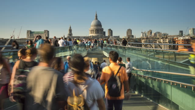 London, people crossing Thames river on Millennium bridge