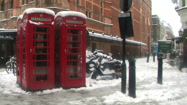 ms london phone boxes covered in snow, london, united kingdom - 電話ボックス点の映像素材/bロール