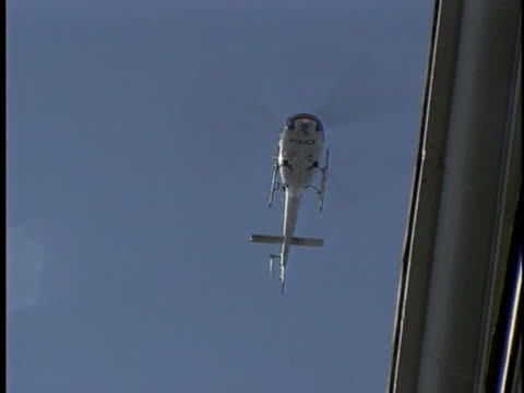 london police helicopter hovers in a blue sky. - helicopter stock videos & royalty-free footage